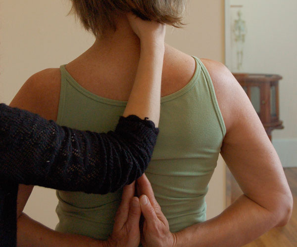 Back on woman, hands in pray pose with Alexander Technique teacher's hand on neck.