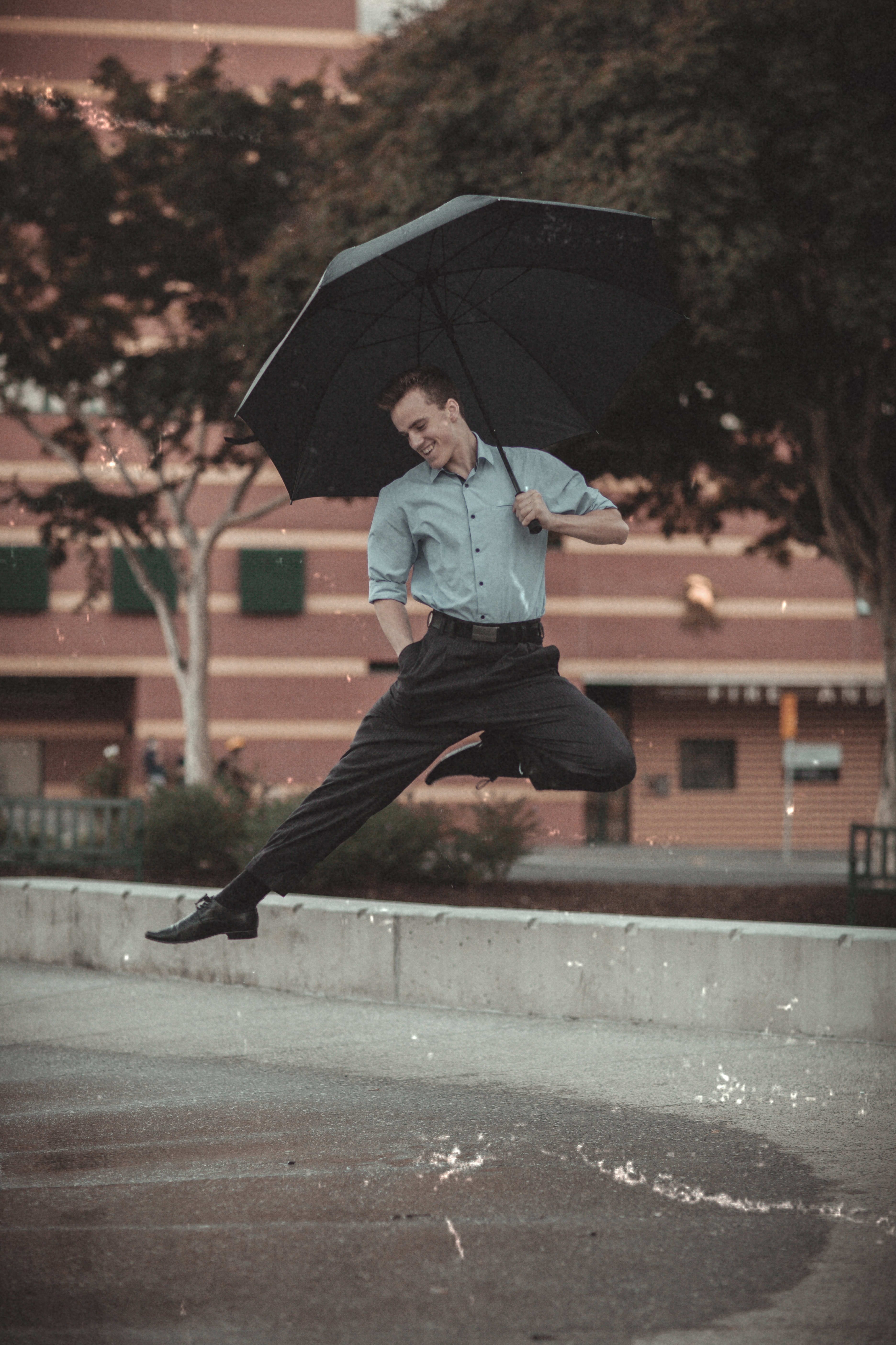 Man leaping while holding an umbrella.